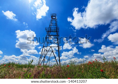 Oil and gas rig profiled on blue sky with clouds
