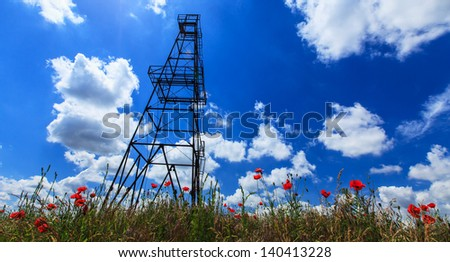 Oil and gas rig profiled on blue sky with clouds - stock photo