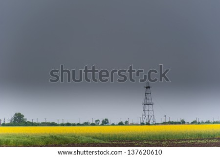 Oil and gas rig profiled over rural canola field