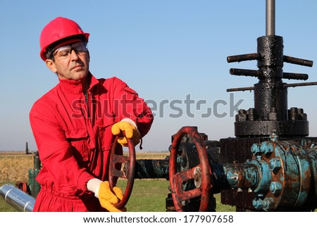 Oil and Gas Well Drilling Worker. Oil industry. Worker turning valve on oil well pump jack. - stock photo