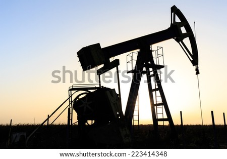 Oil and gas well silhouette in remote rural area, profiled on sunset sky - stock photo