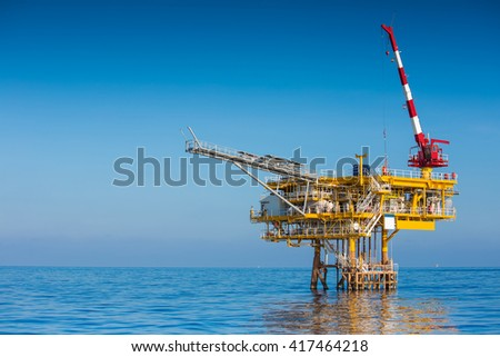 Oil and Gas wellhead remote platform,crane lifting cargo fo loading to supply boat. - stock photo