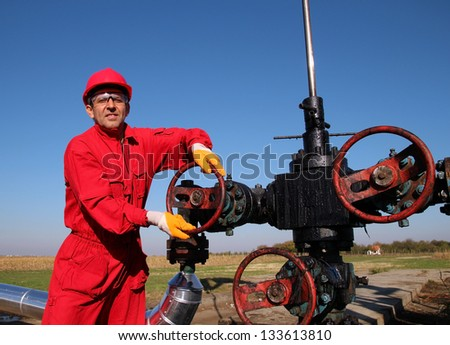 Oil and Gas Worker Wearing Protective Clothing. Smiling oil worker turning valve on oil rig. Oil pump jack in a field. - stock photo