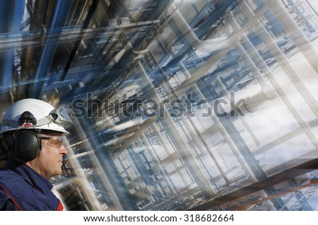 oil and gas worker with giant pipelines construction, slight zoom effect on background - stock photo