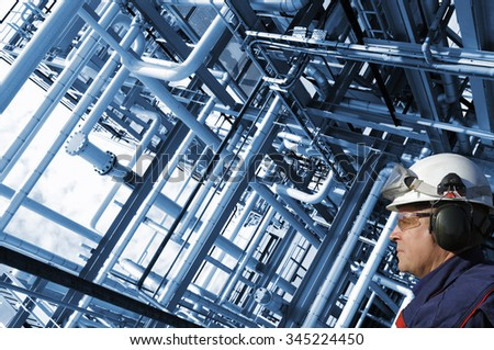 oil and gas worker with large pipelines constructions, inside refinery details - stock photo