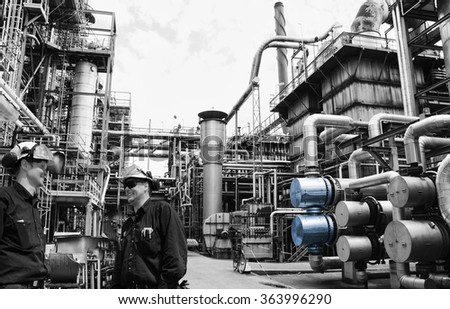 oil and gas workers at main distillery inside large refinery - stock photo