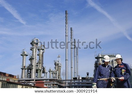 oil and gas workers, engineers, walking in front of refinery industry, wide-angle sharpness. - stock photo