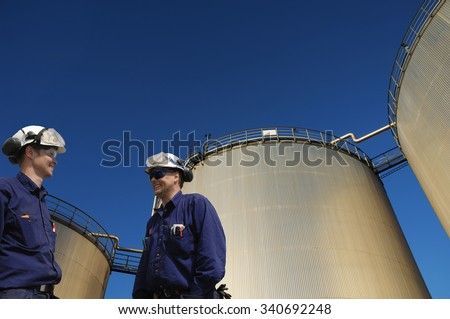 oil and gas workers in front of large fuel storage tanks - stock photo