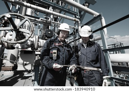 oil and gas workers inside large petrochemical oil refinery - stock photo
