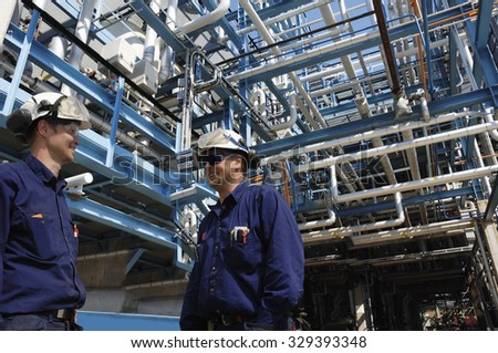 oil and gas workers inside pipelines constructions, refinery industry - stock photo