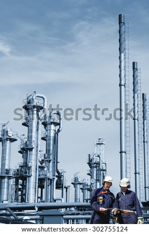 oil and gas workers with large refinery industry in background - stock photo