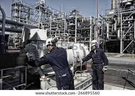oil and gas workers with machinery inside large refinery - stock photo