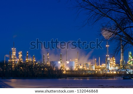 Oil and petroleum refinery along frozen Mississippi River in St. Paul Park Minnesota at night - stock photo