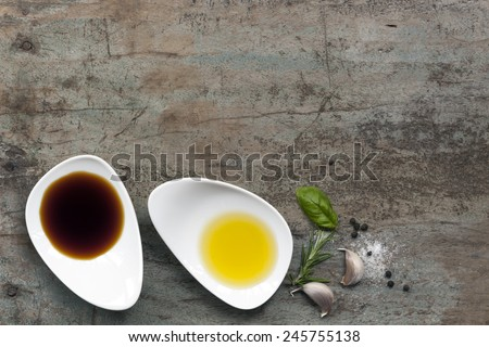Oil and vinegar food background, with peppercorns, salt, garlic and rosemary, over grunge wood. - stock photo