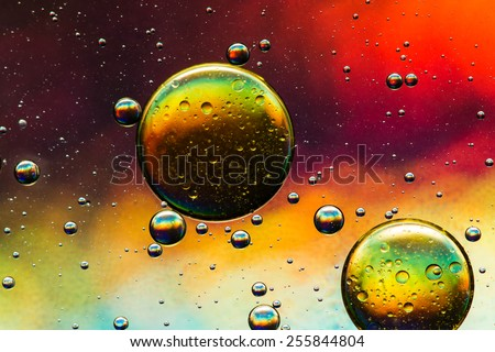 Oil and water abstract in yellow, gold, red, purple and green - stock photo