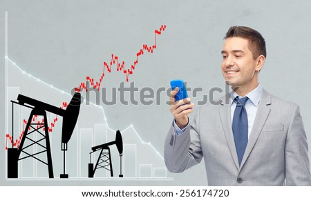 oil business, people, stock market, exchange rate and technology concept - happy businessman texting on smartphone over pump jacks and forex chart gray background - stock photo