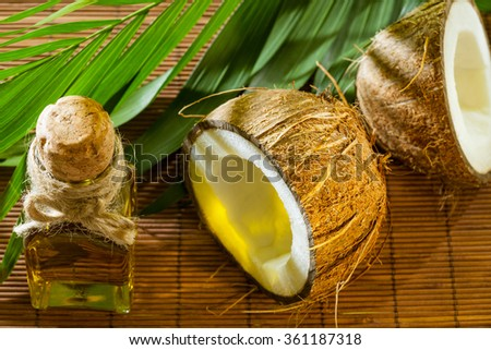 Oil, coconut and green branch on straw background - beautiful spa, haircare and skincare composition in morning sunlight - stock photo