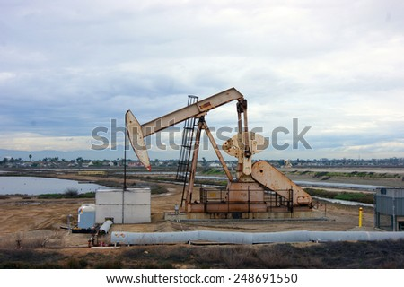 oil derrick with cloudy sky - stock photo