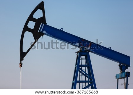 Oil derricks on snowy field at winter time - stock photo
