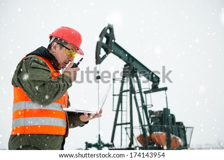 Oil Drill, field pump jack with snow storm and worker. Lens Flare. See more images and video from this series and Refinery series.