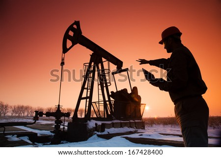 Oil Drill, field pumpjack silhouette with setting sun and worker - stock photo