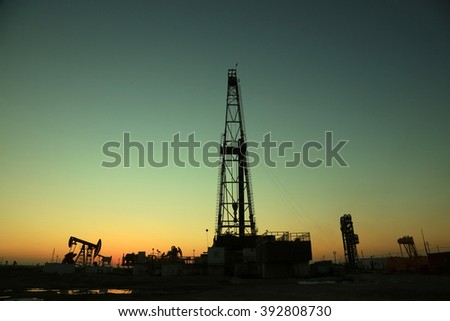 Oil drilling derrick in the sunset