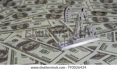oil drilling pump on background of US dollar banknote. Oil business