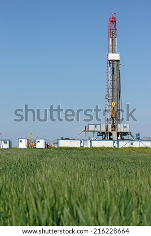 oil drilling rig on green wheat field - stock photo