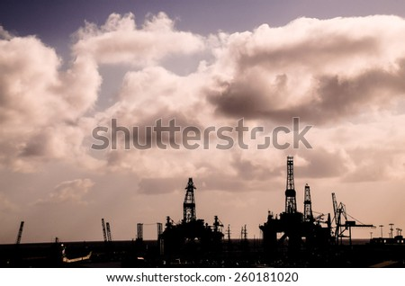 Oil Drilling Rig Silhouette over a Cloudy Sky - stock photo