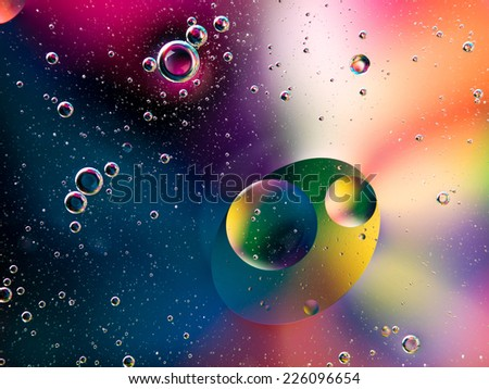 oil drops on water with vivid colorful background - stock photo
