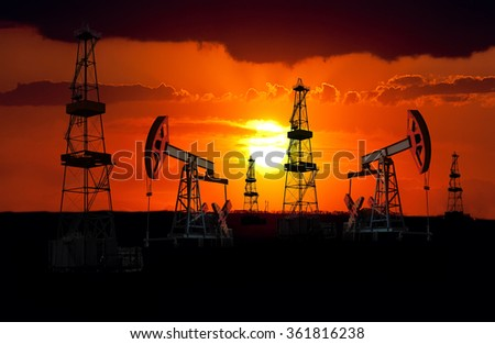 Oil field at sunset. - stock photo