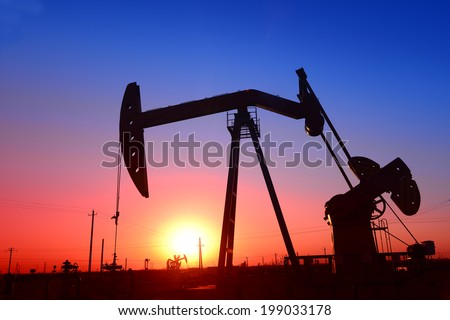 Oil field in an isolated pumping unit under the setting sun