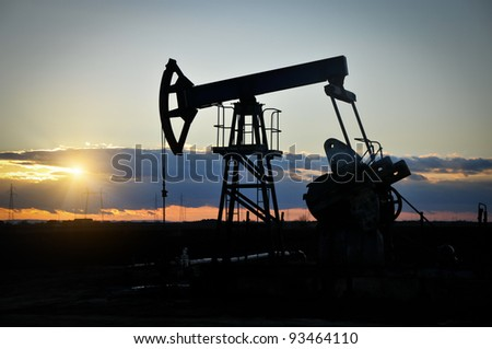 Oil field pump jack silhouette with setting sun. - stock photo