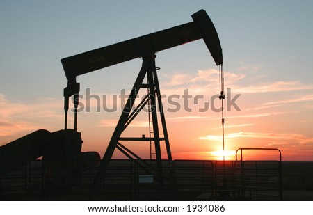 Oil field Pump Jack with setting sun - stock photo