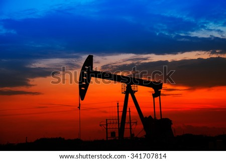 Oil field scene, the evening of beam pumping unit in silhouette - stock photo