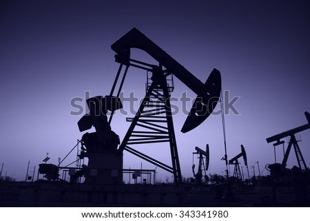 Oil field scene, the evening of beam pumping unit in silhouette