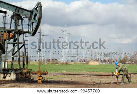 oil field with pump jack and worker - stock photo