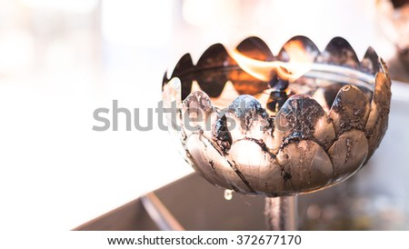 Oil filling in Thai style metal candle at Wat Phra That Doi Suthep Chiang Mai - Thailand - stock photo