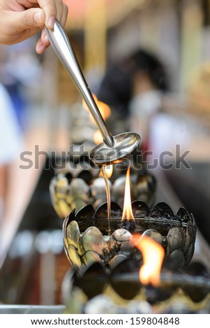 Oil filling in Thai style metal candle in Thai temple, Chiang Mai, Thailand
