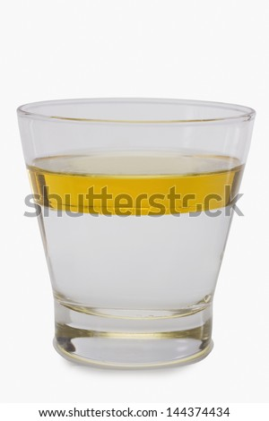Oil floating on water surface in a glass - stock photo