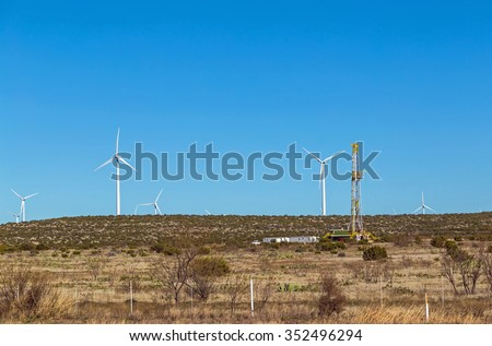 Oil Fracking Rig juxtaposed against field of Wind Turbines, coexisting with the Alternative renewable energy resource. - stock photo