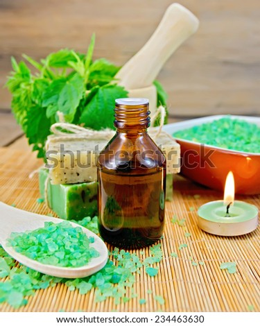 Oil in a bottle, two bars of homemade soap, bath salt, a scented candle, nettle in a mortar on a wooden boards background - stock photo
