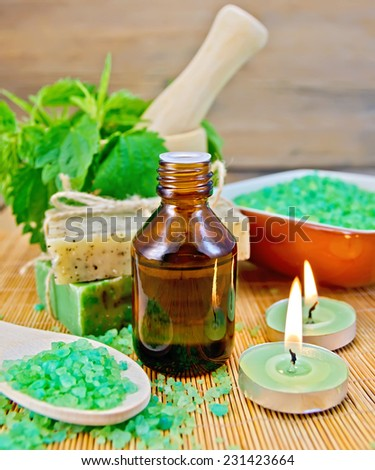 Oil in a bottle, two bars of homemade soap, bath salt, two scented candles, nettles in a mortar on a wooden boards background - stock photo