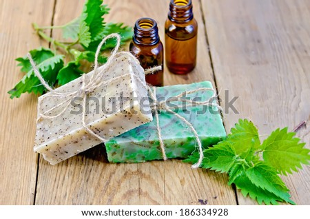Oil in bottles, two bars of homemade soap with twine, nettle on the background of wooden boards - stock photo
