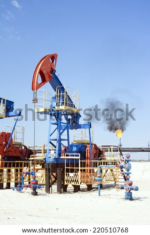 Oil industry and gas industry. Work of oil pump jack on a oil field. Gas torch  - stock photo