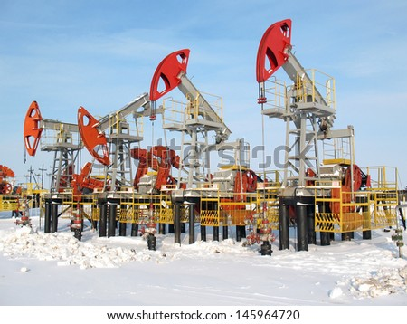 Oil industry and gas industry. Work of oil pump jack on a oil field. Winter extraction of oil - stock photo
