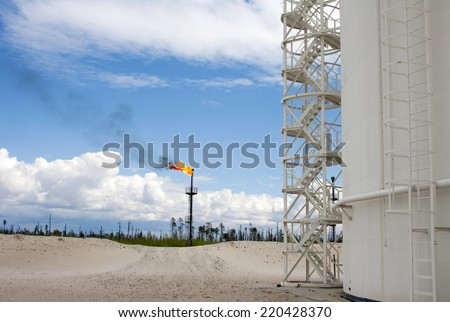 Oil industry. Gas. Oil reservoir and flame torch. Blue sky and white clouds - stock photo