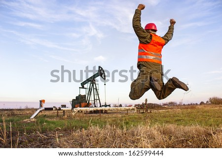Oil Industry Pump jack with one oil worker jumping with joy,best focus on prslku, pockets of pants right hand man and the grass below, copi space, blurred shoes - stock photo