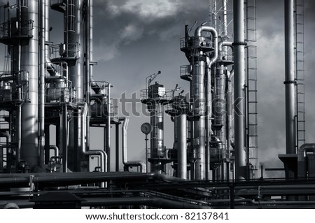 oil industry, refinery installation surrounded by dark clouds, smog and smoke - stock photo