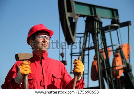 Oil Industry Worker Holding Sledgehammer Next to Pump Jack.Oil industry worker standing next to pump jack, holding sledgehammer and crowbar - stock photo